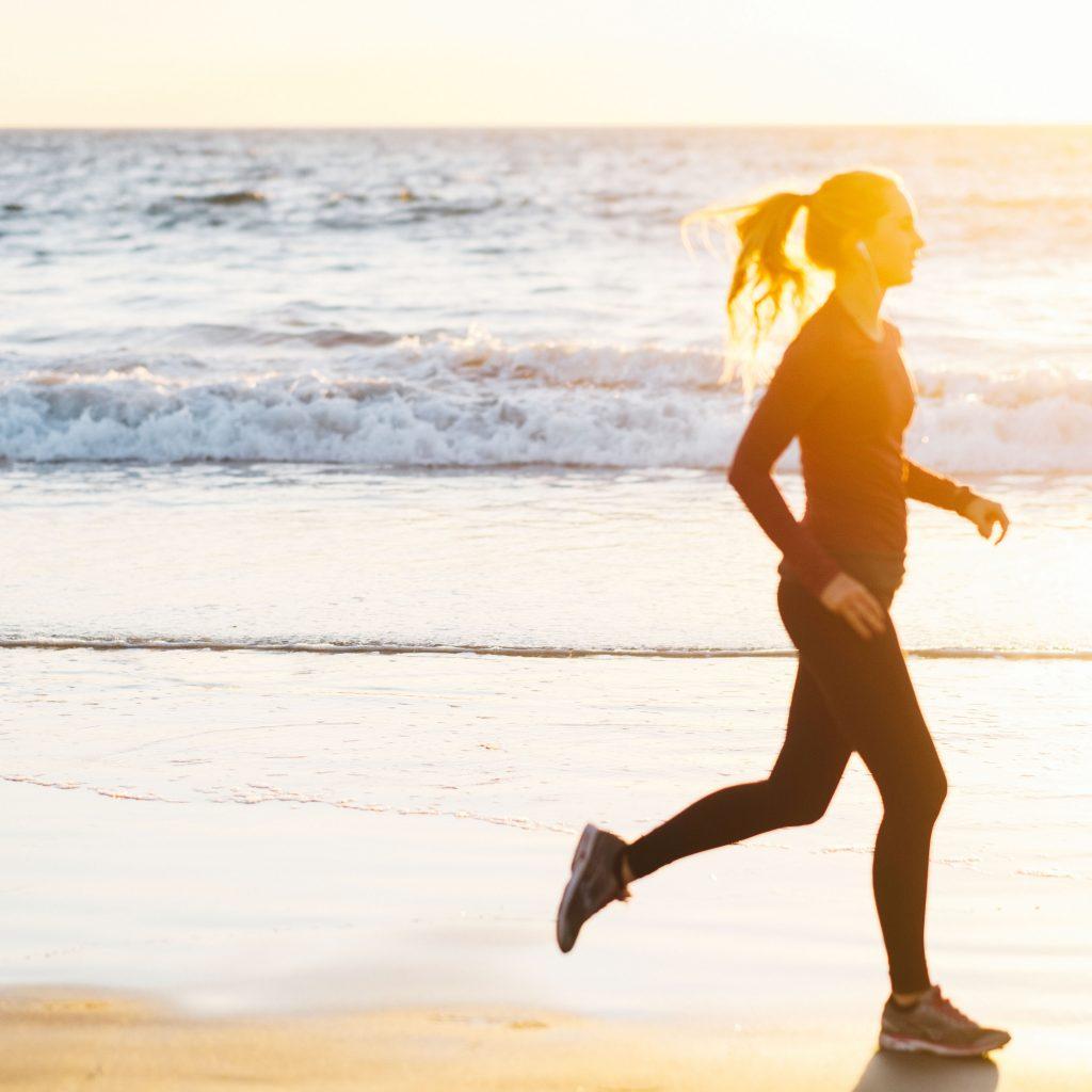Femme jogging sur la plage