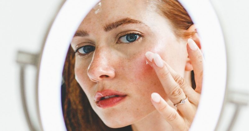 Femme qui se regarde dans un miroir et qui a des rougeurs sur la peau